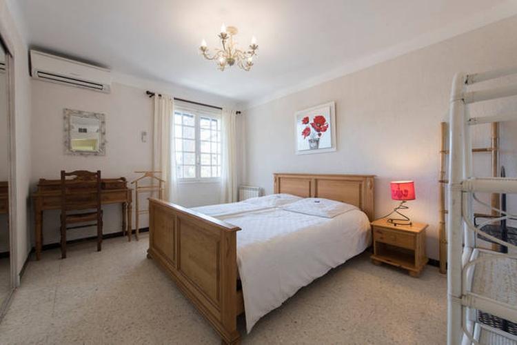 Schlafzimmer mit Doppelbett, Klimaanlage, Waschbecken und Einbauschrank mit Schiebetüren.