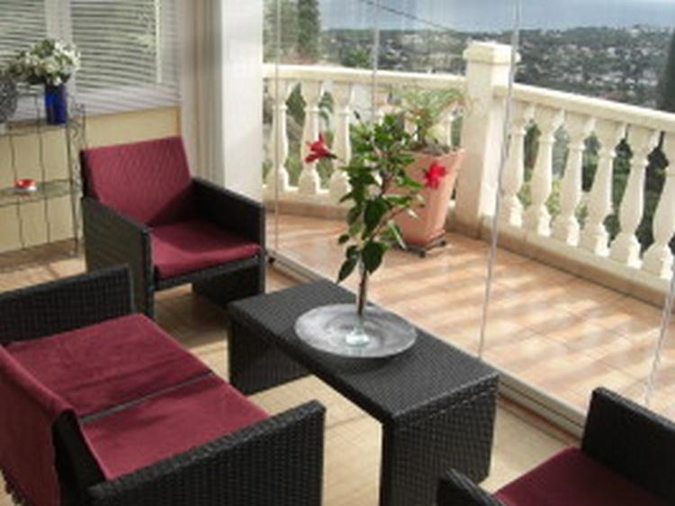 Flexibel veglasbare Südterrasse mit Sitzmöbeln