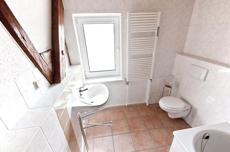 Das Bad mit Badewanne und Fenster.