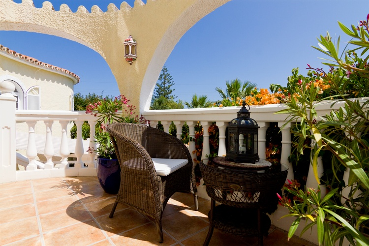 large balcony with many tables and seats, lanterns and umbrellas. Fantastic sea views