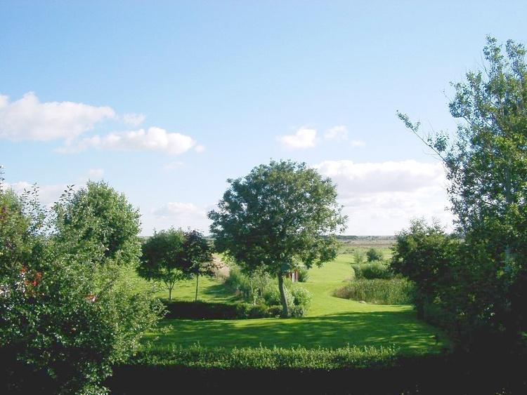 Blick aus dem Haus über den Garten auf die Marsch