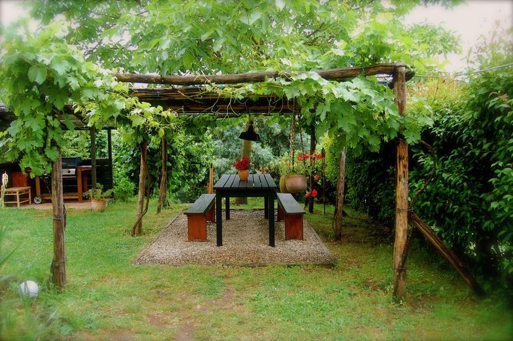 Schattenspendende Pergola mit Tisch und Bänken