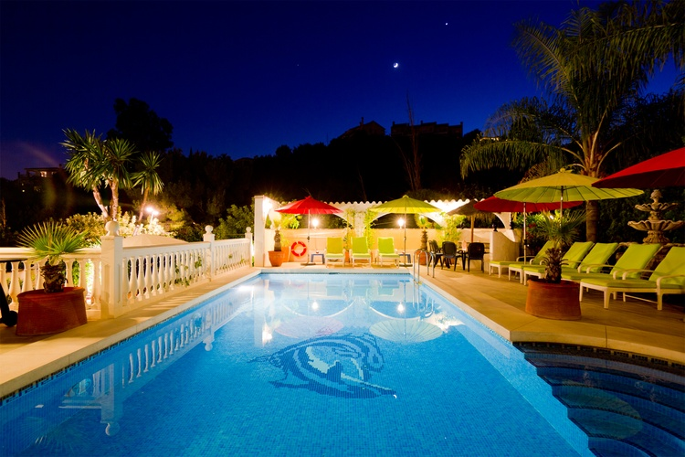 great pool by night with many seat and relax places