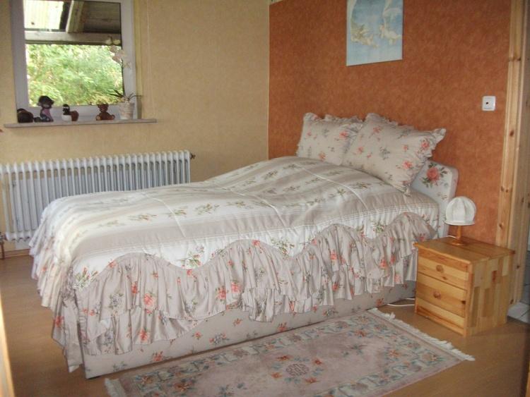 Ein Schlafzimmer der Wohnung Weidenblick mit einem französischem Bett