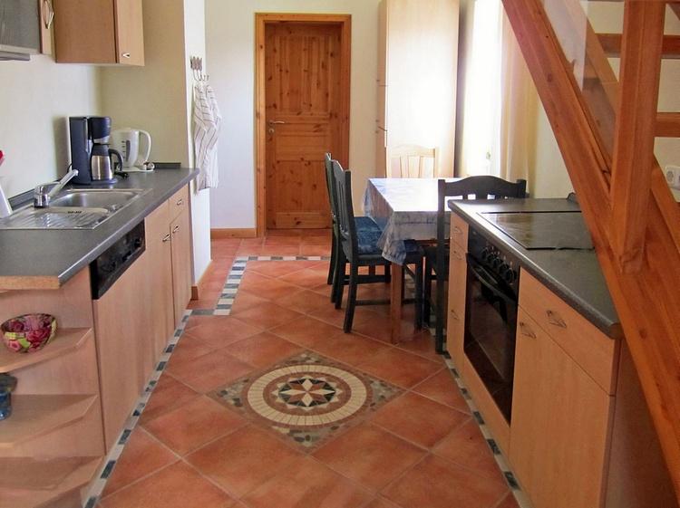Vollausgestattete Küche und Esstisch in Blickrichtung Badtür