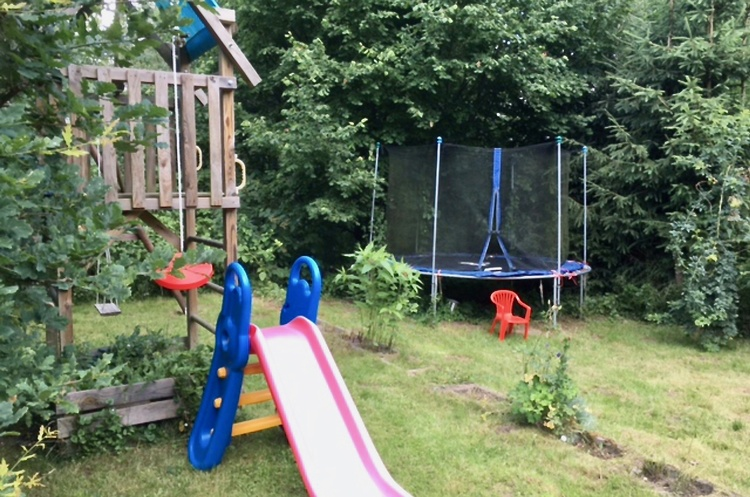 Paradise for children: playground in the garden with swing, slide, climbing tower, trampoline