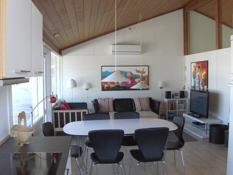 Open access between living room and kitchen. The large windows provide plenty of light. Wood stove