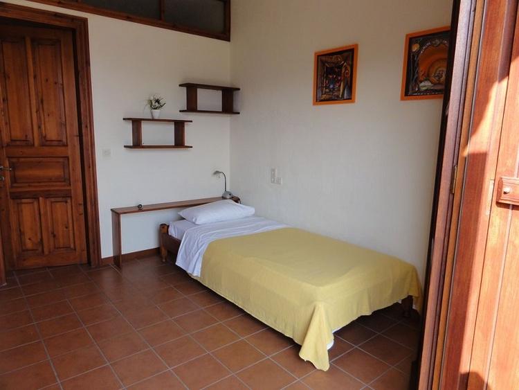 Doppelzimmer mit Einzelbetten und Sitzplatz unter der Pergola