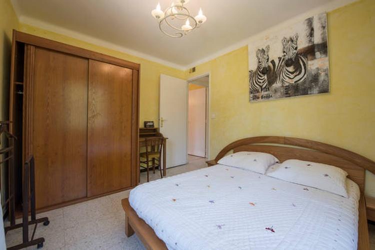 Schlafzimmer mit Doppelbett, Kleiderschrank mit Schiebetüren und Ventilator.
