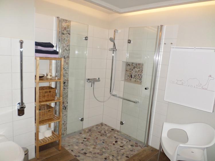 Die ebenerdige Dusche bietet Platz für die ganze Familie. Kosmetikspiegel und Fön gehören mit dazu.