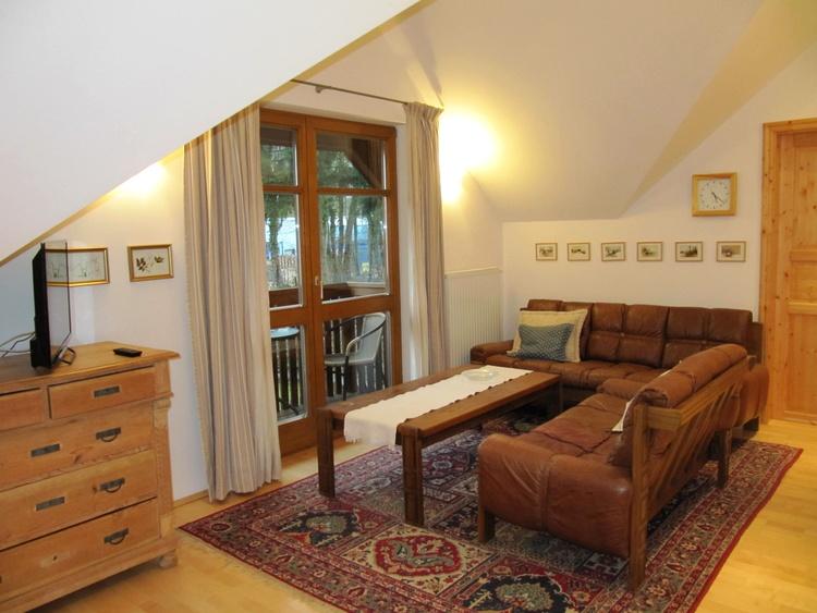 Wohnzimmer mit Sitzgarnitur vor Balkontür
