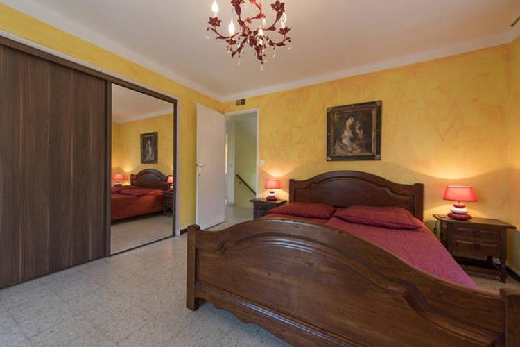 Schlafzimmer mit Doppelbett, Balkon, Klimaanlage und Einbauschrank mit Schiebetüren.